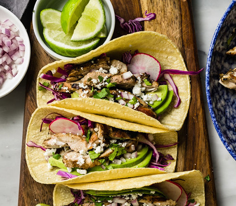 Stock photo of chicken fajita tacos with red cabbage, queso fresco, cilantro, avocado, radish and fresh squeezed lime.